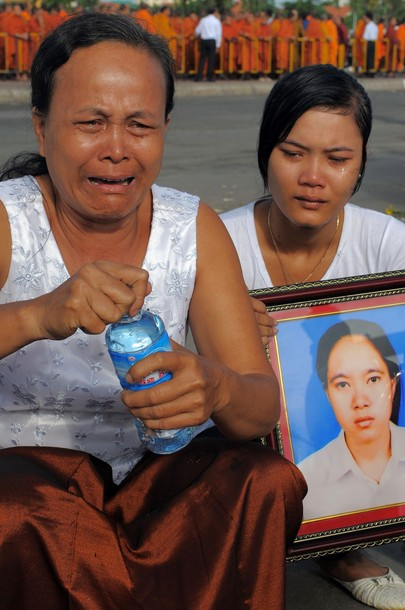 The Cambodian aunt and sister of a vicitim pray for their relative at the Diamond Gate bridge
